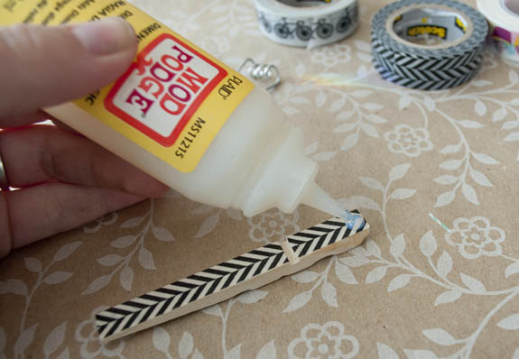 covering washi tape covered clothes pins with diamond glaze to make them shiny and hard