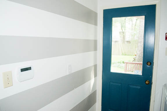 Gray and White stripped wall with peacock blue door.