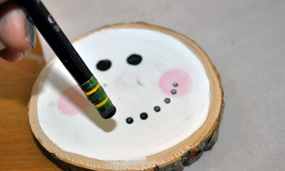 Painting a snowman face with a pencil