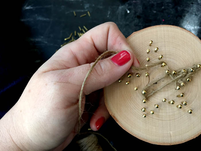 string art on a wood slice to make a christmas ornament